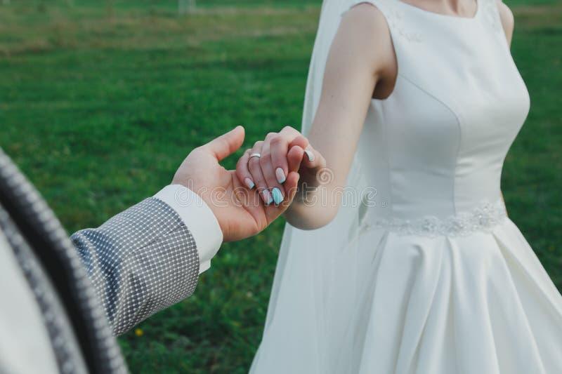 Lo sposo sta tenendo la mano della bella sposa sta stando all'aperto Unghie del manicure di nozze nel colore blu-chiaro tiffany R fotografia stock