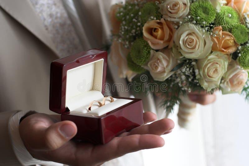 Lo sposo tiene il contenitore di fedi nuziali fotografie stock