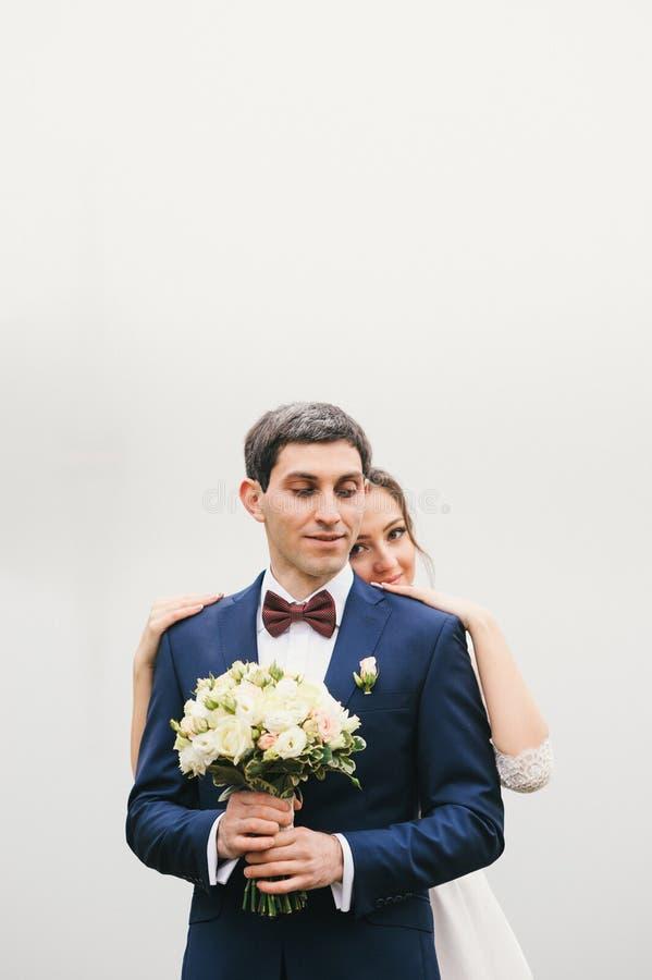 Lo sposo tiene la sposa del mazzo che mette le mani sulle sue spalle fotografia stock