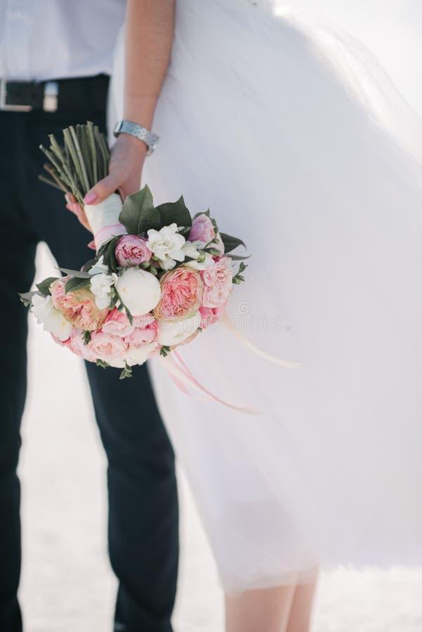 Lo sposo in un vestito abbraccia la sposa in un vestito da sposa fotografie stock