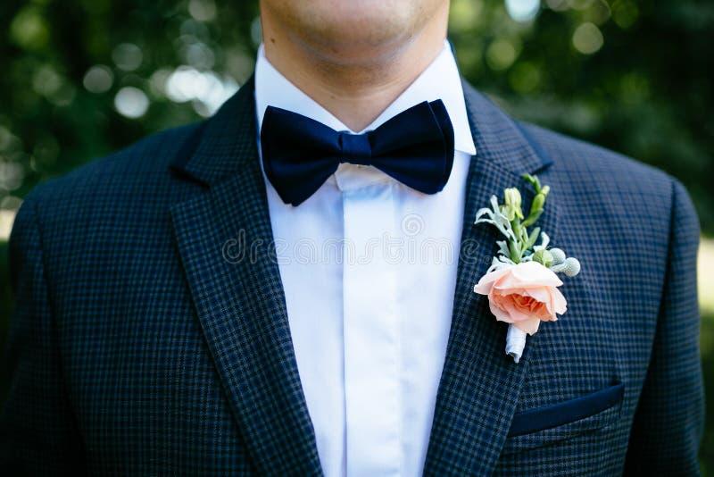 Lo sposo in un vestito blu con un occhiello e una farfalla immagini stock