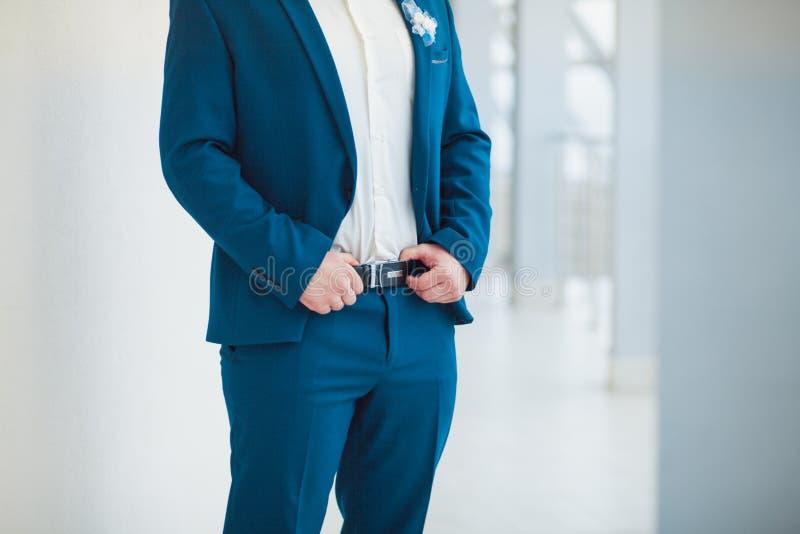 Lo sposo in vestito blu tiene le sue mani sulla cinghia fotografia stock libera da diritti