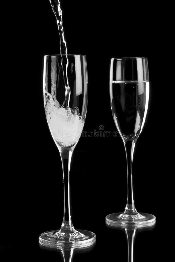 Lo spumante ha versato nelle scanalature di champagne immagine stock