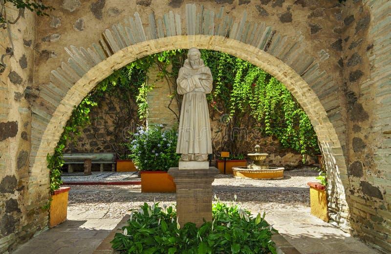 Lo St Francis della statua di Assisi in giardino coloniale fotografia stock libera da diritti
