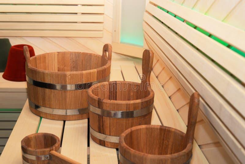 Lo stabilmento balneare di legno con gli strumenti della vasca e del mestolo si chiude su Interno di legno di sauna con attrezzat fotografia stock libera da diritti