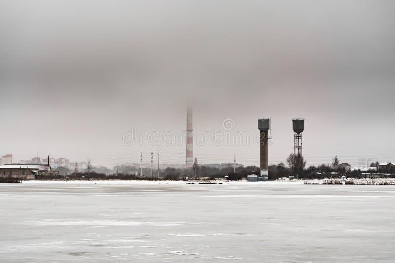 Lo stagno è coperto di ghiaccio, sull'alta costruzione industriale di orizzonte, tempo nuvoloso triste fotografie stock