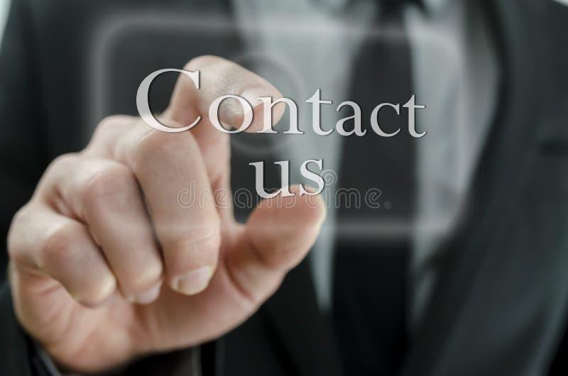 Lo stampaggio a mano dell'uomo d'affari ci contatta bottone sul touch screen fotografie stock