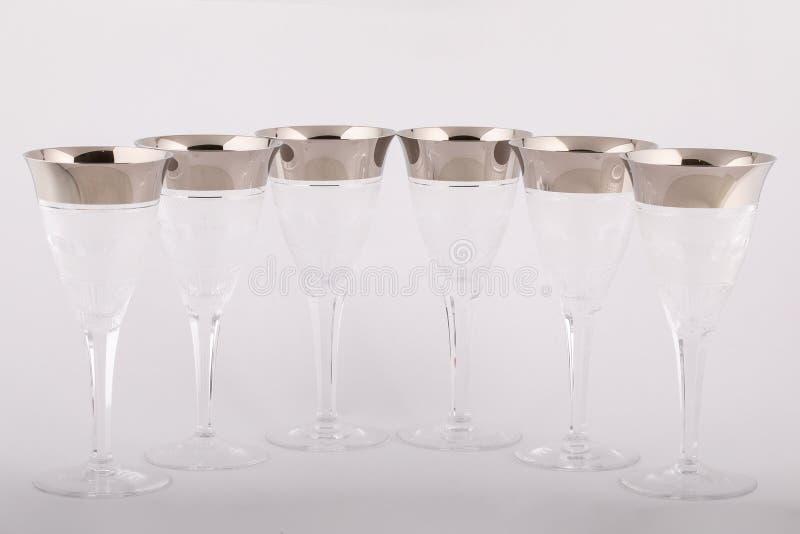 Lo Stemware ha sfaccettato i vetri fatti di vetro ceco con linee d'argento e modelli isolati su un fondo bianco immagine stock