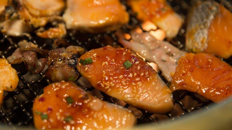 Lo stile coreano ha grigliato il primo piano di color salmone della carne e del pesce sulla stufa calda immagine stock