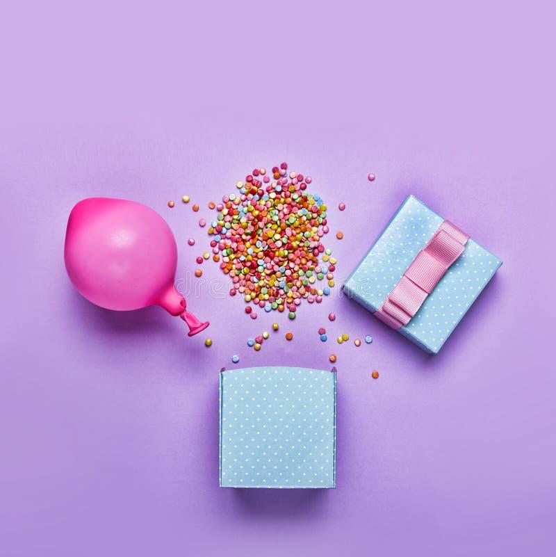 Lo stile di minimalismo, contenitore di regalo blu con i vari coriandoli fa festa, palloni, decorazioni su un fondo verde Backg v fotografie stock libere da diritti