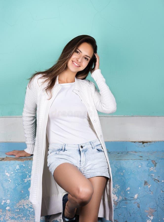 Lo stile ed il modo Ritratto di giovane donna allegra vicino ad una parete luminosa fotografia stock