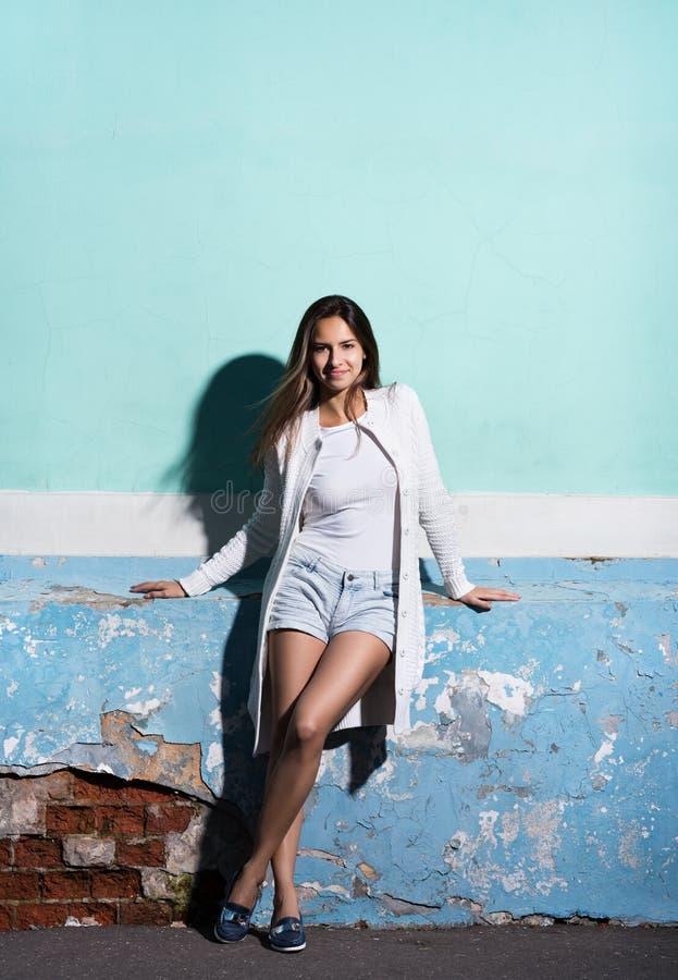 Lo stile ed il modo Ritratto nella piena crescita, bella giovane donna vicino ad un colore luminoso della parete immagine stock
