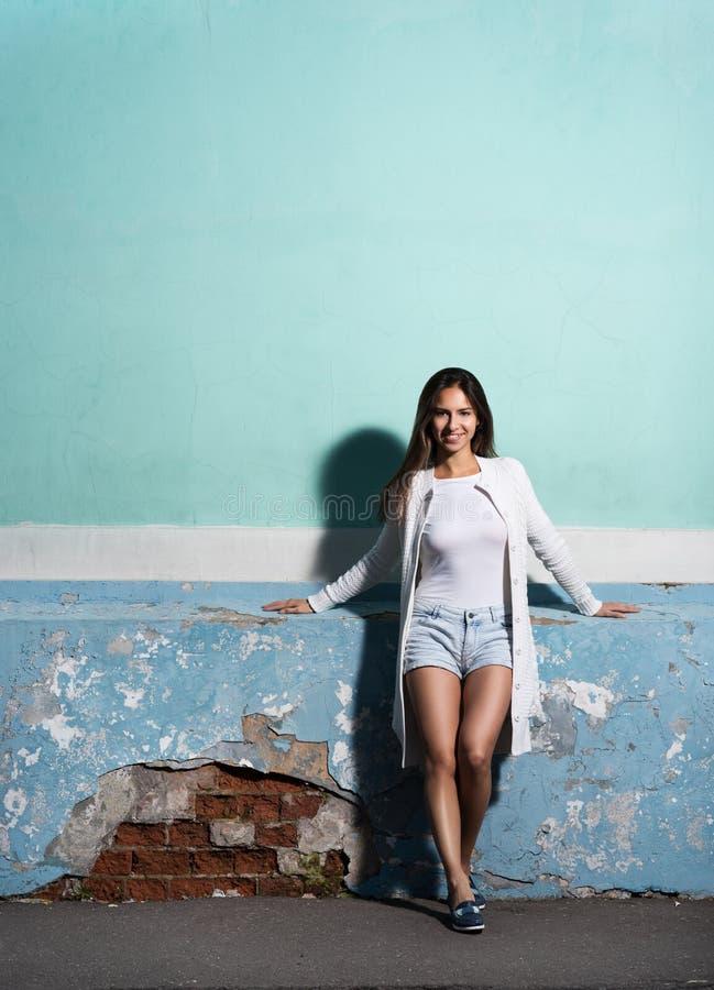 Lo stile ed il modo Ritratto nella piena crescita, bella giovane donna vicino al colore vibrante, la vecchia parete fotografia stock
