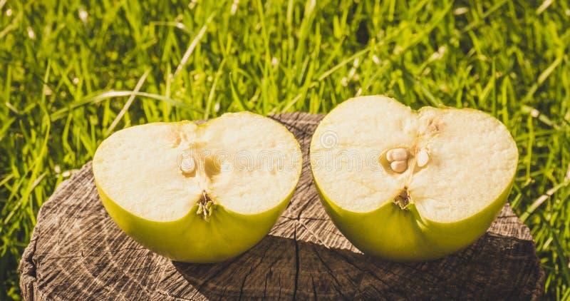 Lo stile rustico Apple a metà verde sui precedenti di vecchio legno fotografia stock
