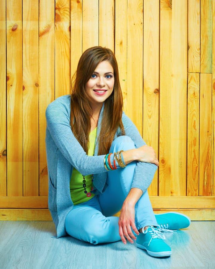 Lo stile sorridente dell'adolescente ha vestito la ragazza che si siede su un pavimento con l'Ass.Comm. immagine stock