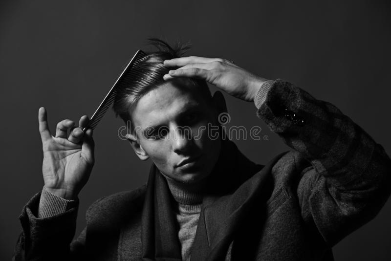 Lo stilista con il fronte serio fa l'acconciatura Uomo nello stile d'annata immagini stock libere da diritti