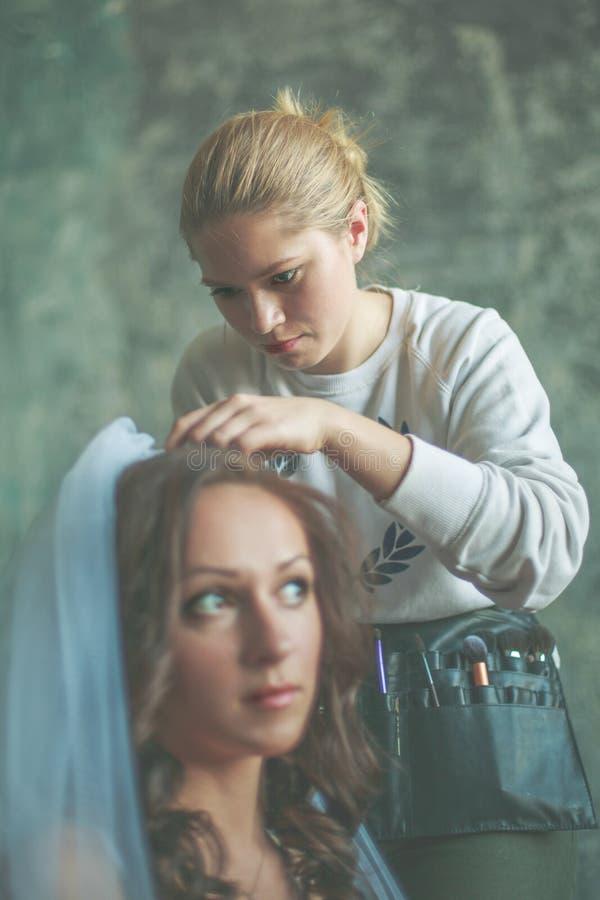 Lo stilista di capelli fa la sposa immagine stock libera da diritti