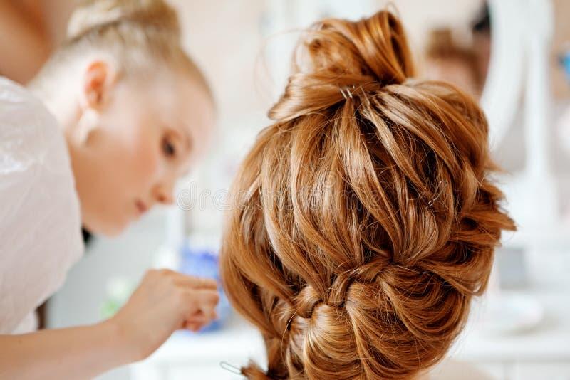 Lo stilista di capelli fa la sposa prima delle nozze fotografia stock