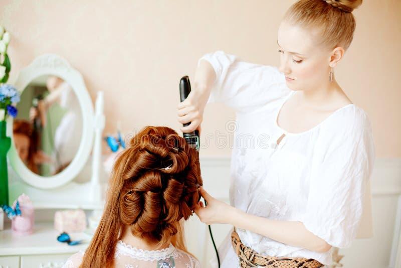 Lo stilista di capelli fa la sposa sul giorno delle nozze immagine stock
