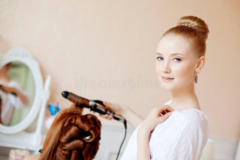 Lo stilista di capelli fa la sposa sul giorno delle nozze immagini stock