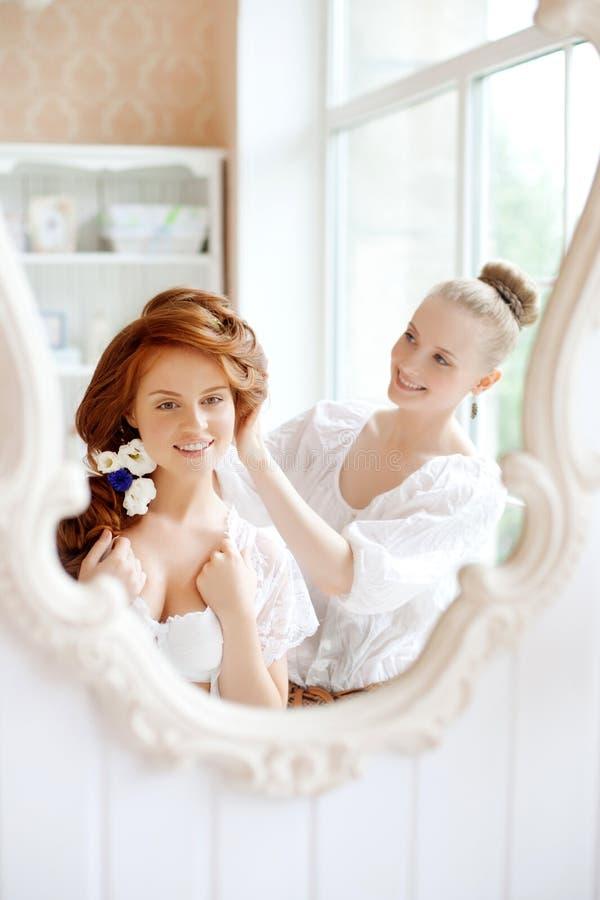 Lo stilista di capelli fa la sposa sul giorno delle nozze fotografia stock