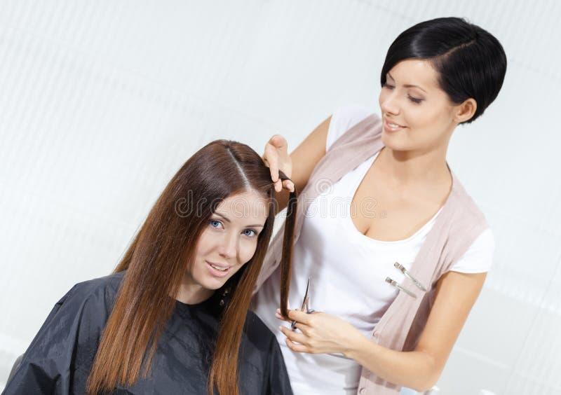 Lo stilista di capelli taglia i capelli della donna in parrucchiere fotografia stock