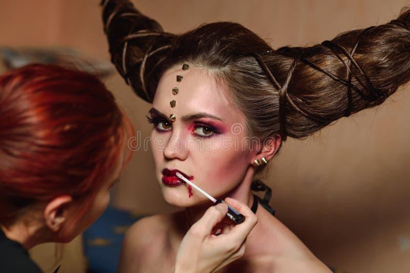 Lo stilista fa il trucco di Halloween, spazzolante il sangue sulle labbra dei modelli fotografia stock