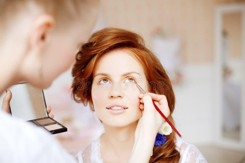 Lo stilista fa la sposa di trucco prima delle nozze fotografia stock libera da diritti