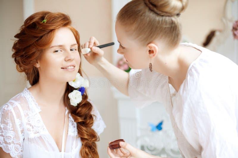 Lo stilista fa la sposa di trucco prima delle nozze immagine stock libera da diritti