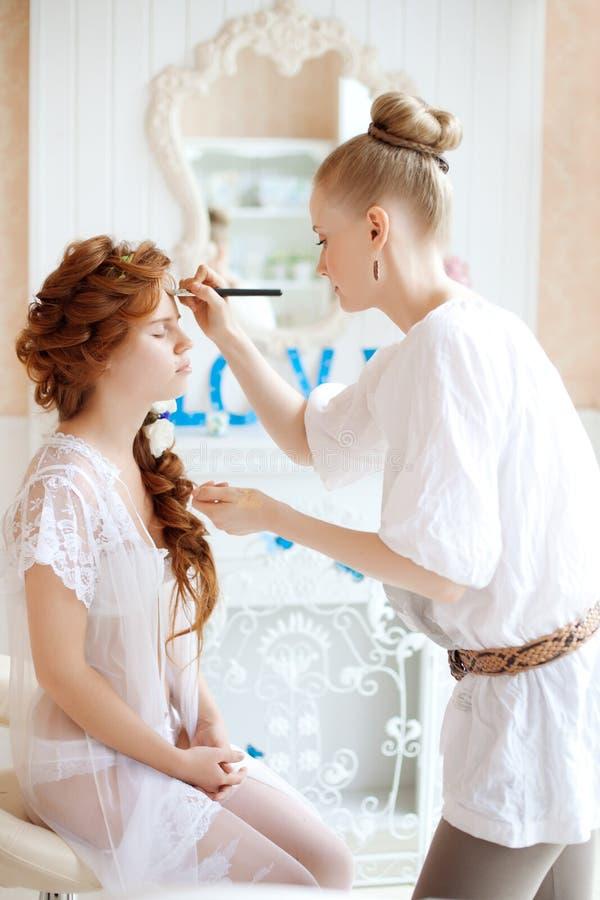Lo stilista fa la sposa di trucco sul giorno delle nozze fotografie stock