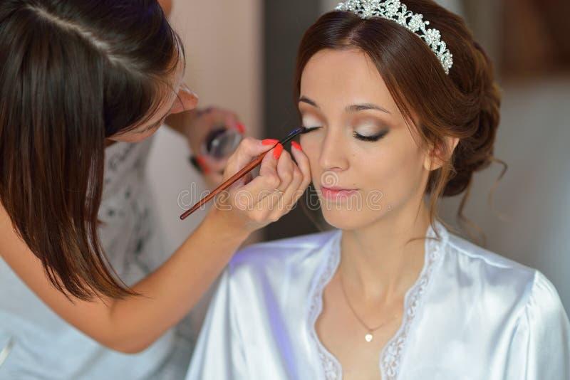 Lo stilista fa la sposa di trucco sul giorno delle nozze fotografia stock libera da diritti