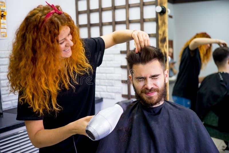 Lo stilista finisce il taglio di capelli fotografie stock
