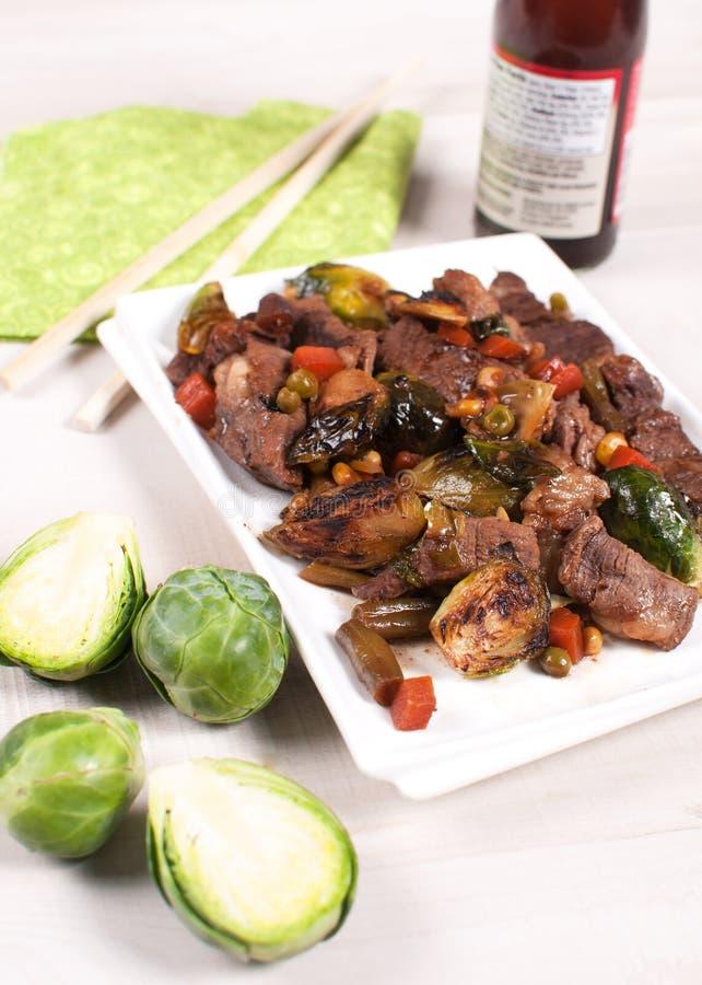 Lo stir asiatico ha fritto i cavolini e le verdure di Bruxelles con carne fotografia stock