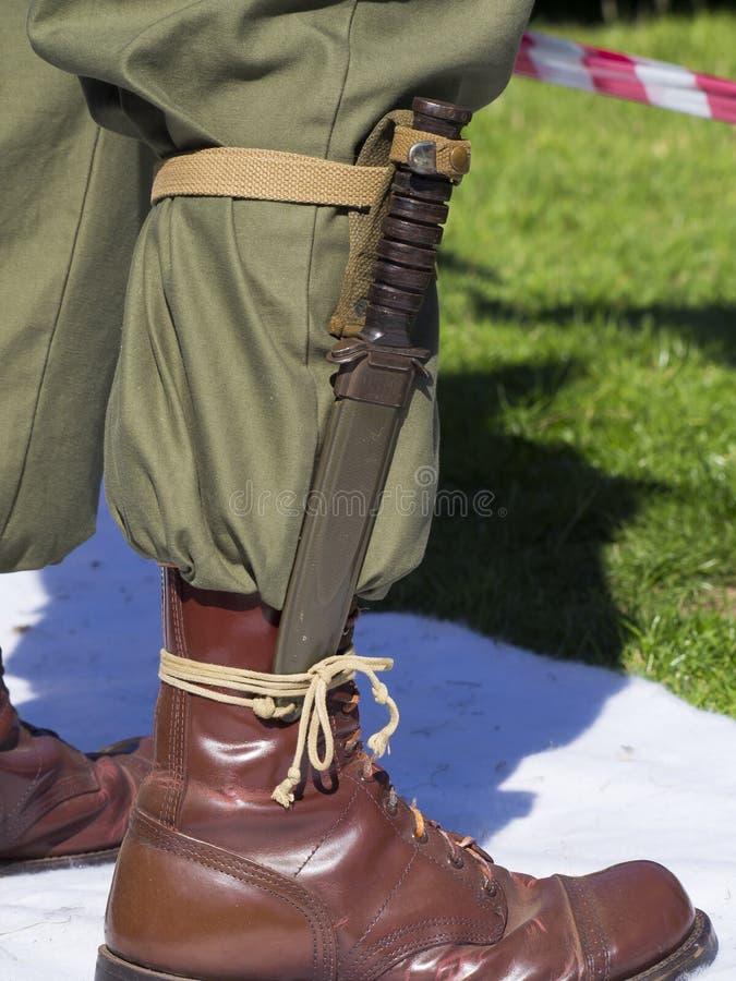 Lo stivale dell'esercito con il pugnale della baionetta ha attaccato a  fotografia stock