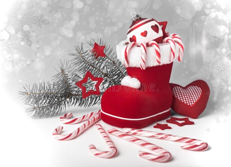 Lo stivale di Santa con i bastoncini di zucchero e le decorazioni di natale fotografia stock libera da diritti