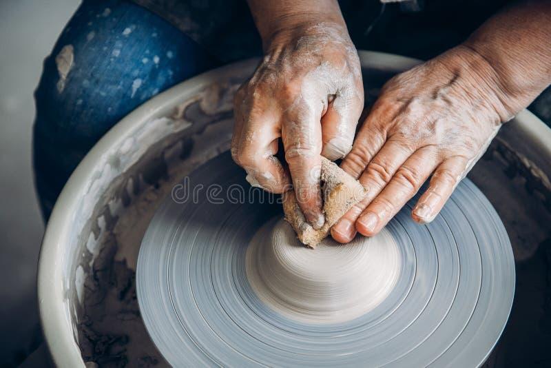 Lo stregone corrugato delle mani sul tornio da vasaio fa i piatti dell'argilla Posto da lavorare Vista superiore immagini stock libere da diritti