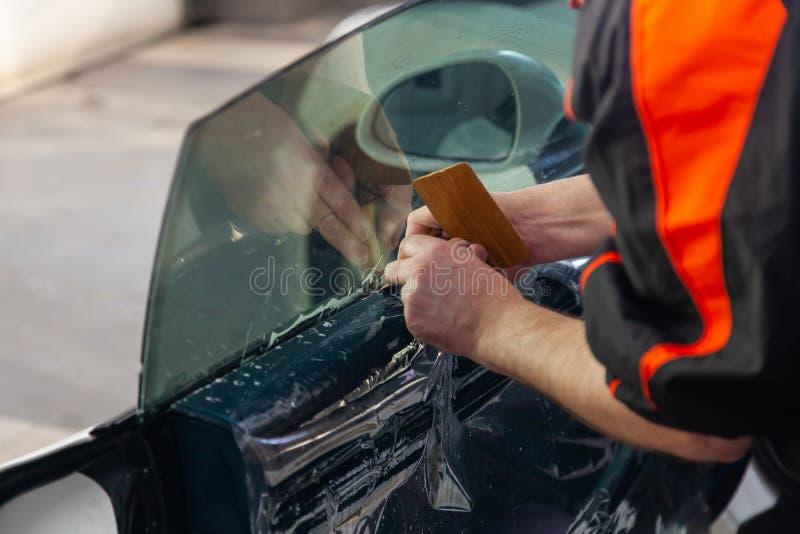 Lo stregone per l'installazione dell'attrezzatura supplementare attacca un film della tinta sul vetro anteriore laterale dell'aut immagini stock libere da diritti