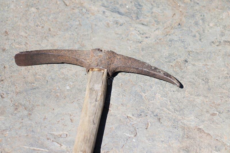 Lo strumento del piccone si trova sulla pietra Estrazione del piccone dell'attrezzatura del minerale di ferro e della pietra con fotografie stock