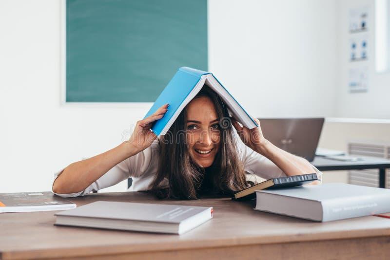 Lo studente allegro nasconde la sua testa sotto il libro sotto il libro fotografia stock