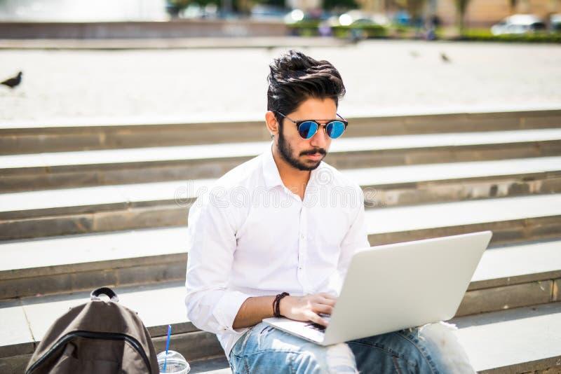 Lo studente di college americano indiano orientale si siede sulle scale sulla città universitaria, lavora al computer portatile n immagine stock libera da diritti