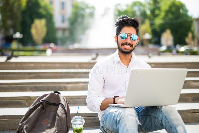 Lo studente di college americano indiano orientale si siede sulle scale sulla città universitaria, lavora al computer portatile n immagini stock libere da diritti