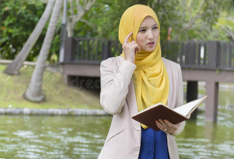 Lo studente di college grazioso gode di di leggere e ritenere nel parco fotografia stock libera da diritti