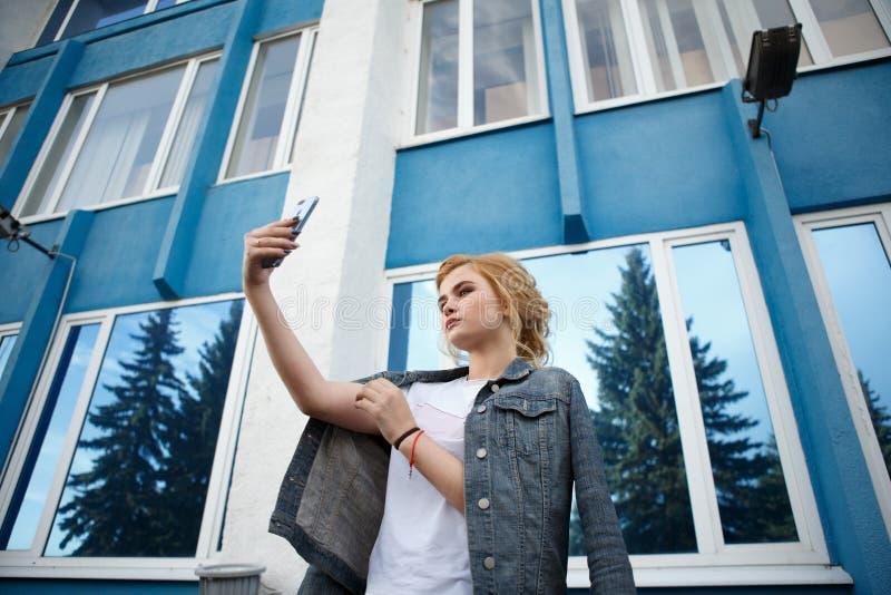 Lo studente fa un autoritratto con uno smartphone, bei pantaloni a vita bassa della ragazza che prendono le immagini se stessi co fotografia stock