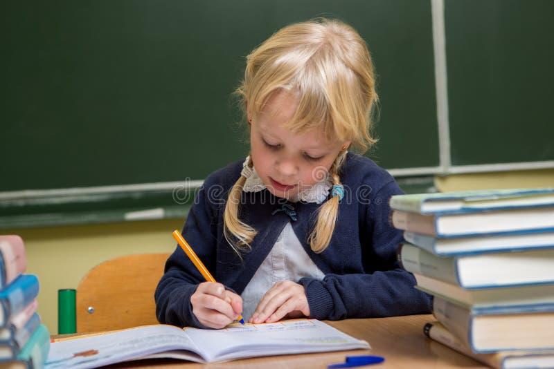 Lo studente lavora in un'aula della scuola, bambino alla scuola, fotografia stock