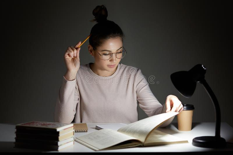 Lo studente occupato assorbente nella lettura, dura intorno ai vetri trasparenti per la buona visione, utilizza la lampada di let immagine stock libera da diritti