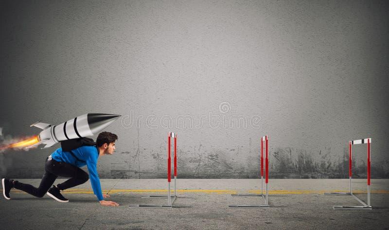 Lo studente supera gli ostacoli dei suoi studi a massima velocità con un razzo fotografia stock