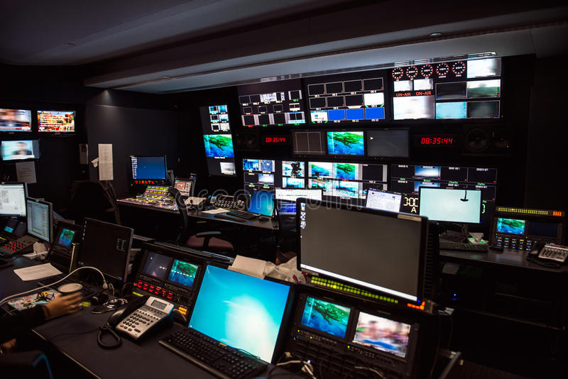 Lo studio di notizie di trasmissione televisiva con molti schermi di computer ed i pannelli di controllo per aria in tensione han fotografia stock libera da diritti