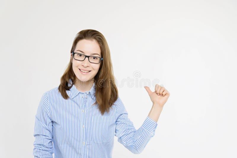 Lo studio ha sparato alla giovane ragazza graziosa che indica con il pollice fotografia stock