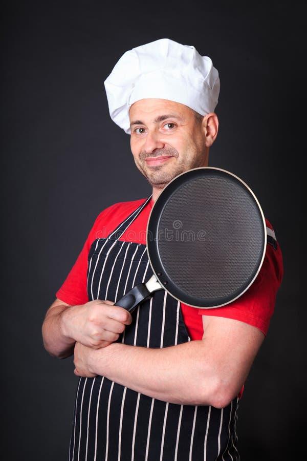Lo studio ha sparato del cuoco unico positivo con una padella immagini stock