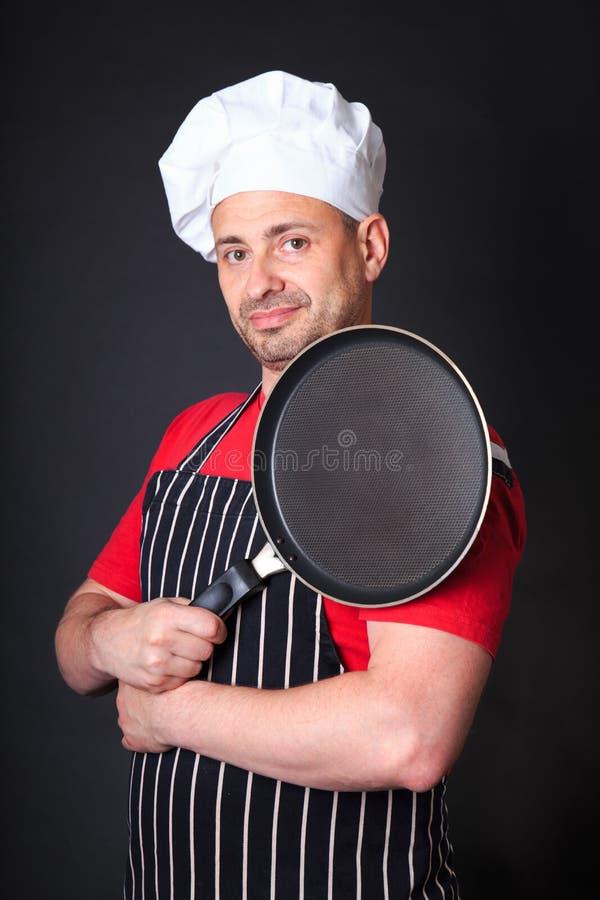 Lo studio ha sparato del cuoco unico positivo con una padella immagine stock libera da diritti